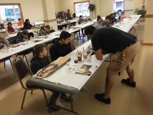 Ron Fairbanks teaching kids how to paint formline. (Aaron Bolton, KSTK News)