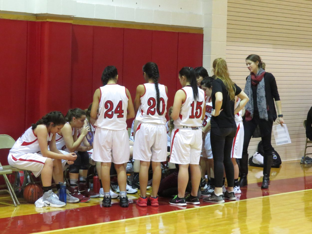 Varsity girls basketball team huddles