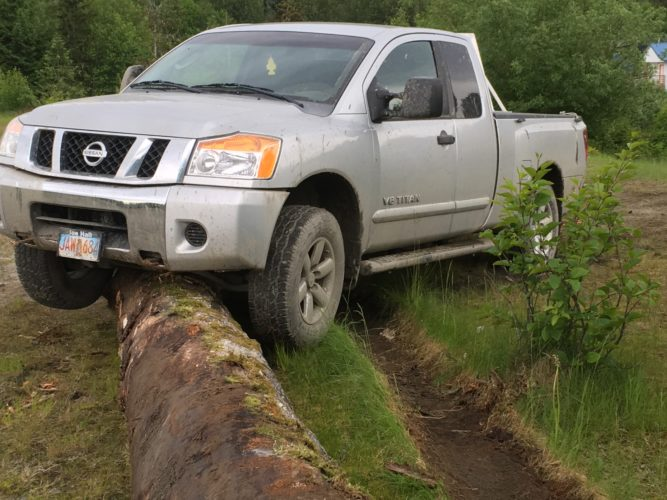 A man police say stole and damaged about eight vehicles in the past week left this truck high-centered on a large log. (Photo courtesy Wrangell Police Department)