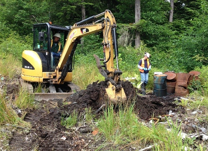A backhoe digs up part of the old Byford Junkyard in Wrangell. After removing old cars, oil drums and other trash, the state is treating and moving contaminated soil to a rock quarry south of town. (Photo courtesy Department of Environmental Conservation)
